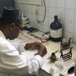 Lab technician analyzing slides in Dakar, Senegal.
